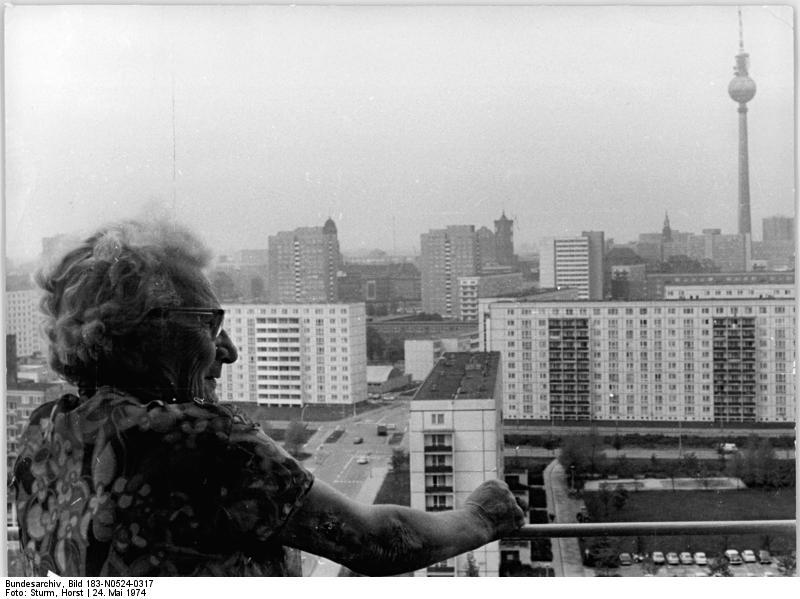 """Blick über die Stadt vom Balkon einer Neubauwohnung aus. Neben Alten, Ausreise-Antragstellern und Aussteigern gehörten alleinerziehende Mütter zu den prekären """"A""""s des Ostens, Berlin, 24. Mai 1974. Foto: Horst Sturm (ADN). Quelle: Bundesarchiv Bild 183-N0524-0317 / Wikimedia Commons https://commons.wikimedia.org/wiki/File:Bundesarchiv_Bild_183-N0524-0317,_Berlin,_Neubauten,_Fernsehturm.jpg?uselang=de CC BY-SA 3.0 https://creativecommons.org/licenses/by-sa/3.0/de/deed.en"""