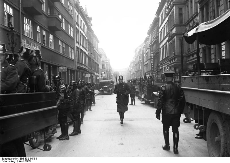 """Berliner Schutzpolizei und nationalsozialistische Hilfspolizei durchsuchen das Berliner Judenviertel in der Grenadierstraße und Dragonerstraße."" (Original-Bildunterschrift: Aktuelle-Bilder-Centrale, Georg Pahl) Fotograf unbekannt, April 1933. Quelle: Bundesarchiv, Bild 102-14481 https://commons.wikimedia.org/wiki/File:Bundesarchiv_Bild_102-14481,_Berlin,_Judenviertel,_Durchsuchung.jpg, Lizenz: CC BY-SA 3.0 DE https://creativecommons.org/licenses/by-sa/3.0/de/deed.en"